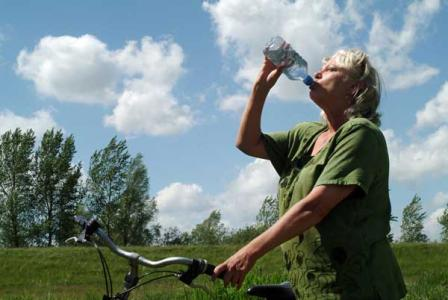 woman on bicycle drinking